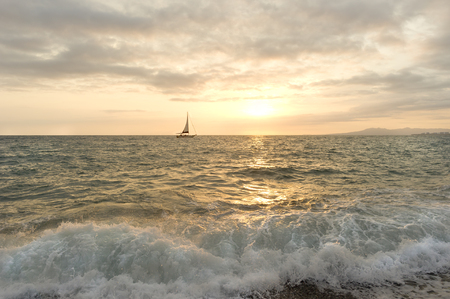 sailboat: Sailboat sunset is a sailboat sailing the seas while a golden ocean wave crashes on shore. Stock Photo
