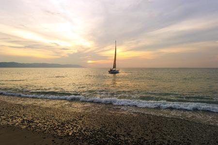 ヨット日没は圧延ソフト波と海の地平線に太陽の沈む海岸近くに乗って人を持つ帆船です。 写真素材