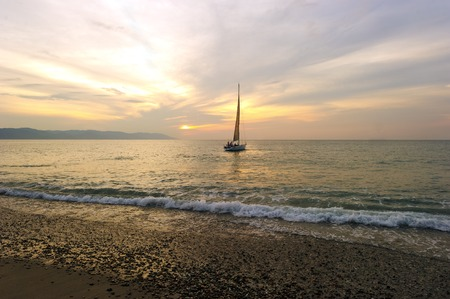 sailboat: Sailboat Sunset is a sailboat with people aboard close to shore with a soft wave rolling in and the sun setting on the ocean horizon.