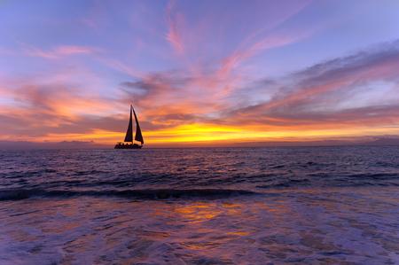 ヨット日没のシルエットは、カラフルな鮮やかなオレンジ色と黄色の cloudscape の夕日です。
