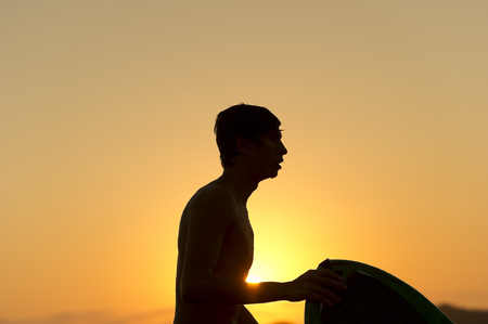 water dripping: Surfer is a silhouette of a surfer and his board at sunset with water dripping off his face. Stock Photo
