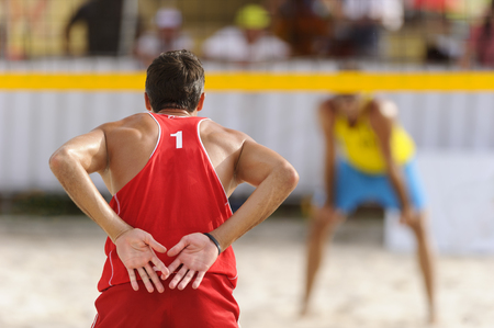 volleyball serve: Volleyball player is a male volleyball player giving signals to his partner as his opponent waits for the serve.