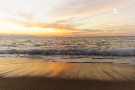 Ocean waves is brightly light golden seascape with waves rolling to the shore as scattered sunbeam break through a dramatically onto the ocean horizon. 写真素材
