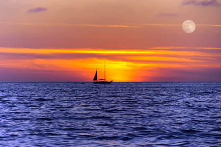 colorful cloudscape: Sailboat sunset silhouette is a colorful vibrant orange and yellow cloudscape sunset with a full moon rising in the sky..