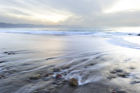 rocks water: Ocean absrtact is a scenic of ocean water rushing back to the sea around colorful beach rocks on the shore.