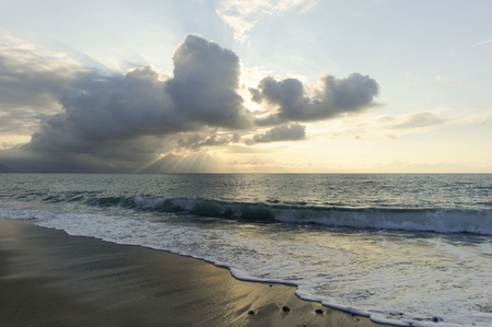dramatically: Ocean sun rays is brightly light golden seascape with waves rolling to the shore as scattered sunbeam break through a dramatically onto the ocean horizon.