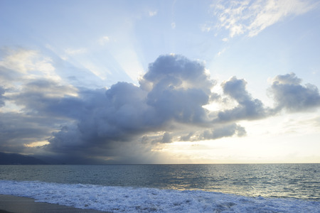 dramatically: Sun ray clouds is lit brightly light golden seascape with waves rolling to the shore as scattered sunbeam break through a dramatically onto the ocean horizon. Stock Photo