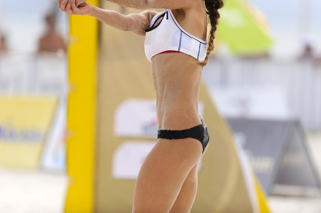 recieve: Volleyball player is a fit strong female athelete recieving serve in a beach volleyball match. Stock Photo