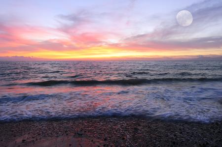 La puesta del sol del océano es brillantemente iluminada y el paisaje marino dorado con una suave ola rodando hacia la orilla y una luna llena que se eleva en el cielo.