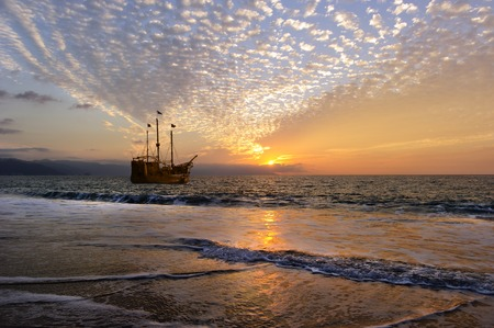 Pirate Ship is an old wooden pirate ship with full flags as the sun sets on the ocean horizon in a colorful sunset sky.