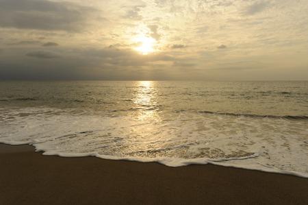 ビーチの夕日は、波の穏やかな海岸にローリングで黄金海景明るい光です。 写真素材