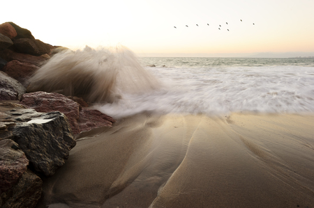 waves crashing: Waves crashing is an ocean seascape with a wave crashing up against a rock throwing water into the air as birds fly in the background..