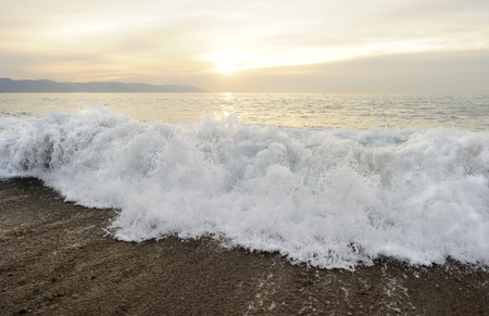 Wave breaking is a seascape with a wave breaking on the shore as the sun sets in the background.