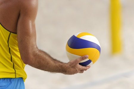 male athlete: Volleyball player is a male athlete volley ball player getting ready to serve the ball.