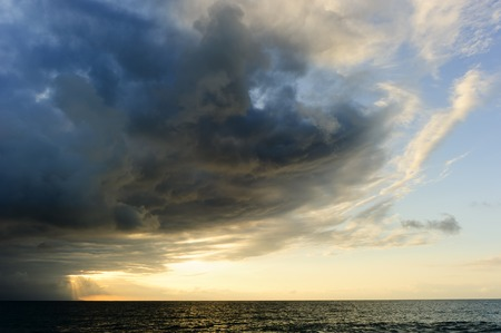 sunrays: Storm clouds is an ominous storm moving in over the ocean as a bright set of sunrays burst through the darkness to light the way.