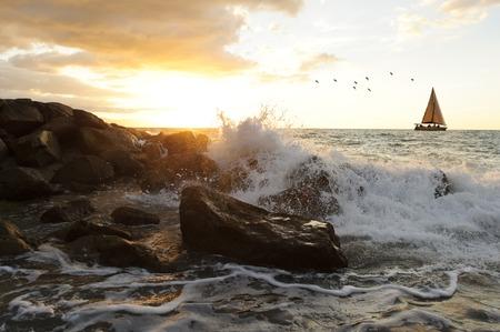 olas del barco de vela es un paisaje marino del océano con una ola chocando contra un agua de lanzamiento de piedras en el aire como un barco de vela mueve a lo largo del horizonte del océano .. Foto de archivo