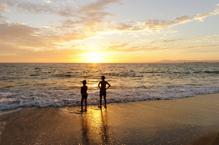 Boys beach sunset is silhouettes of two boys watching with awe as the sun sets with a beautiful orange blaze.