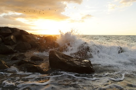 Olas rompiendo es un paisaje marino del océano con una ola chocando contra un agua de lanzamiento de piedras en el aire. Foto de archivo