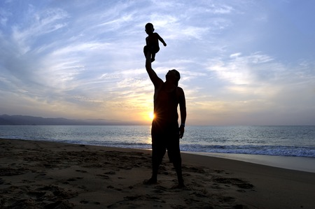 Father son is a silhouette of a father joyfully loving  his son at the beach at sunset.