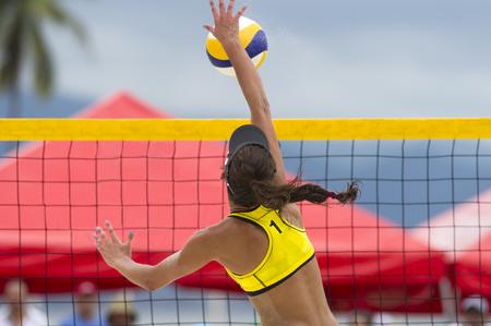 Volleyball-Spieler ist ein weiblicher Spieler Athleten Volleyball zum Netz aufsteigt, den Ball mit dem Hammer nach unten.