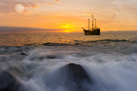 Ocean sunset ship fantasy is a brightly lit golden seascape with a pirate ship anchored at sea with the full moon rising in the sky as a gentle wave rolls to the shore.