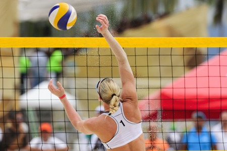 Volleyball player is a female athlete beach volleyball player rising up to make a play on the ball..