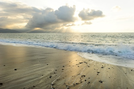 uplifting: Ocean sun beams is a bright uplifting seascape with sun rays breaking through the clouds as a gentle wave rolls to shore. Stock Photo