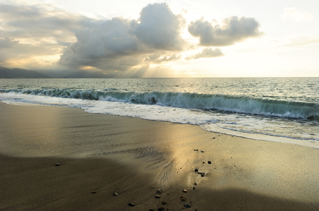 uplifting: Ocean sunset sun rays is a bright uplifting seascape with sun beams breaking through the clouds as a gentle wave rolls to shore.