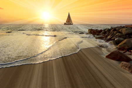 A sailboat is sailing on the ocean as a burst of brilliant light beams emanates for the sun.