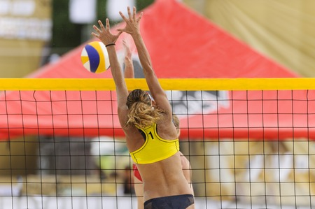 Volleyball player is a female athlete beach volleyball player rising up to battle her opponent at the net. Stock Photo