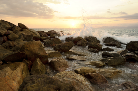 breaking wave: Ocean wave splash is a sunset seascape with rocks near the shore as a breaking wave sprays up in the air.