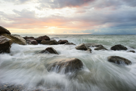 Ocean sunset is a beautiful scenic seascape with waves rushing and flowing through the sturdy ocean landscape.