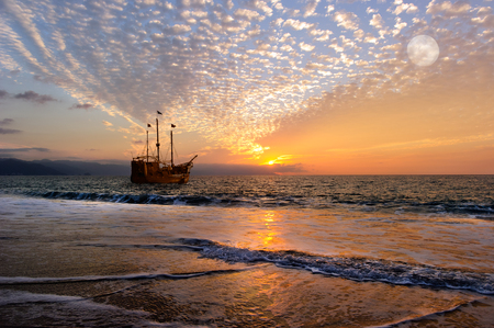 海賊船ファンタジーは、カラフルな夕焼け空に海の水平線に沈む完全フラグと古い木造の海賊船です。