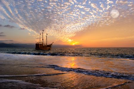 Nave pirata fantasia è una vecchia nave pirata in legno con bandiere piene come il sole tramonta all'orizzonte oceano in un cielo colorato tramonto. Archivio Fotografico - 65287866