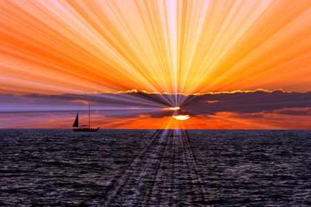 filled out: Sunset sailboat is a silhouetted boat sailing along the ocean water withe a sun burst of rays flowing out from behind the colorful cloud filled sky.