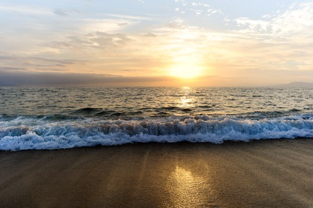 amanecer: Sunset ocean is a wave rolling to shore as sun sets on the ocean horizon.