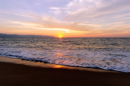 Ocean sunset is a brightly lit golden seascape with a gentle wave rolling to the shore.