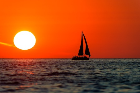 boat crew: Sunset sailboat is a silhouetted boat with crew aboard sailing along the ocean water with a white hot sun setting in the red sunset sky.