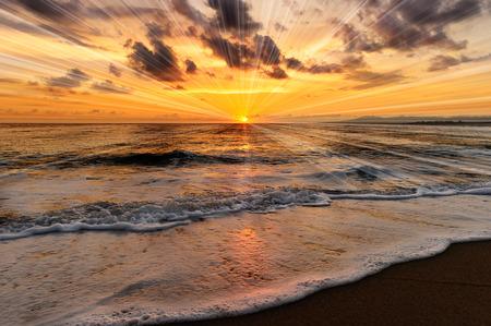 Los rayos de la puesta del sol del océano son rayos brillantes del sol en el horizonte del océano y una onda apacible que rueda hacia la playa. Foto de archivo