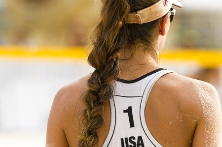 Volleyball player serving is a female beach volleyball player getting ready to serve the ball.