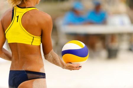 Volleyballspieler, der dient, ist ein weiblicher Strandvolleyballspieler, der bereit ist, den Ball zu dienen. Standard-Bild - 83533074