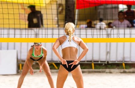 Volleyball player is a female beach volleyball player giving hand signals to her team mate while she faces her opponent across the net.