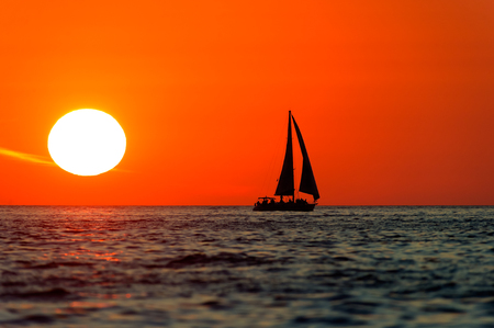 Ocean sunset ocean sailing is a silhouette of a sailboat and its crew sailing along the ocean water at sunset. Stock Photo