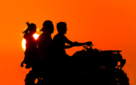 Quad bike is an ATV with three people riding silhouetted against the sunset sky having fun. Stock Photo