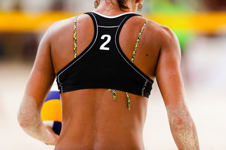 Volleyball beach player serving is a female beach volleyball player getting ready to serve the ball. Stock Photo