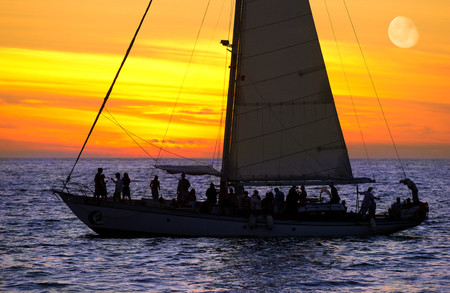 Sailboat sunset party is a group of people having a good time ocean sailing at sunset.