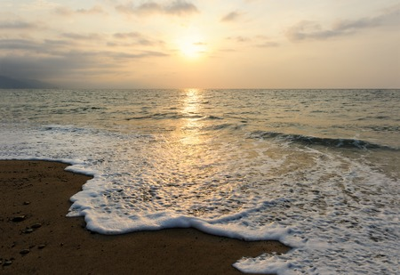 Ocean Sunset is a golden reflection off a gentle wave rolling to shore as the sun sets in the cllou filled sky.