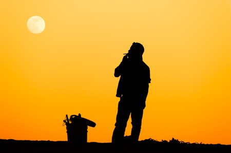 Man smoking silhouette is a silhouette of a man smoking a cigarette against the orange background of a sunset sky.