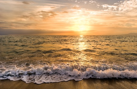 Ocean sunset is an ocean sunset wave rolling to shore as the sun sets on the ocean horizon.
