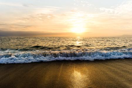 La puesta del sol del océano es una onda de la puesta del sol del océano que rueda a la orilla mientras que el sol se pone en el horizonte del océano. Foto de archivo